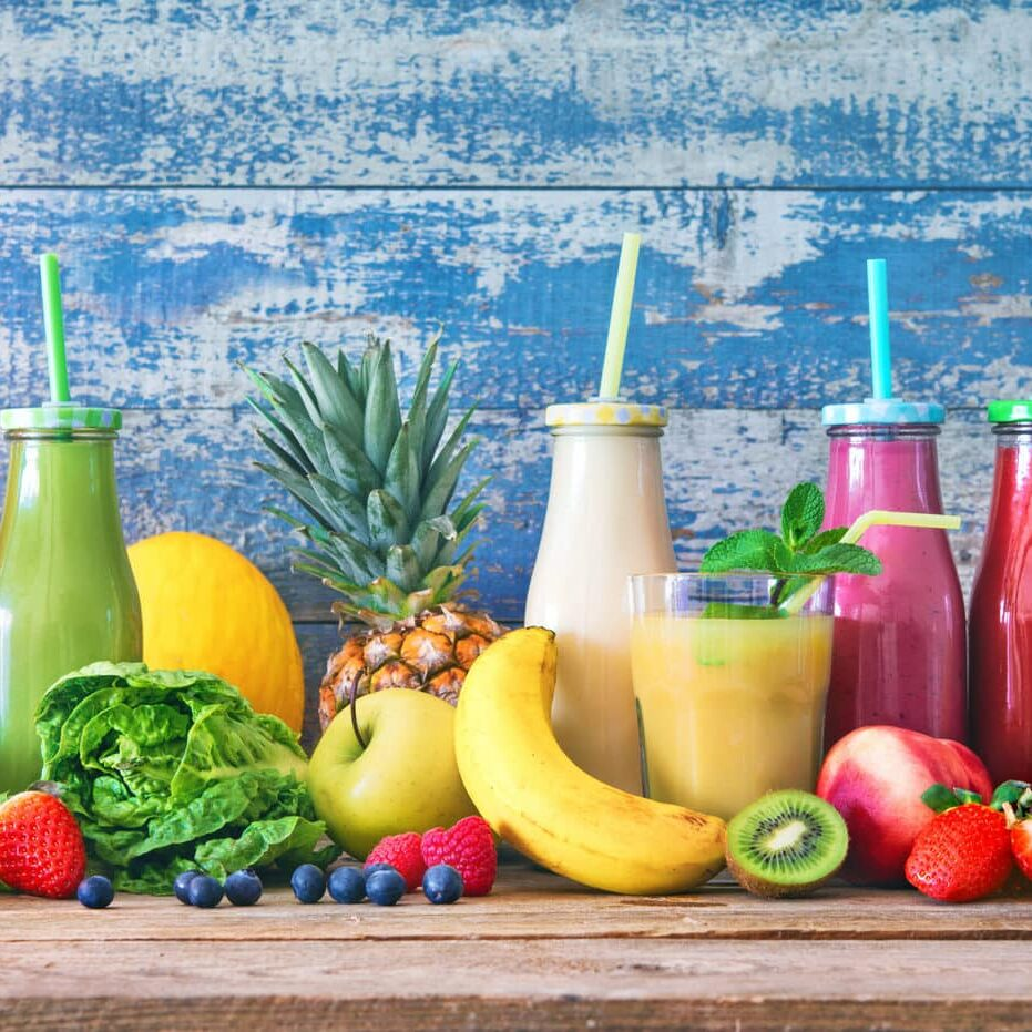 Colorful freshly squeezed fruits and vegetables smoothies with ingredients for healthy eating. Detox, dieting or healthy food concept