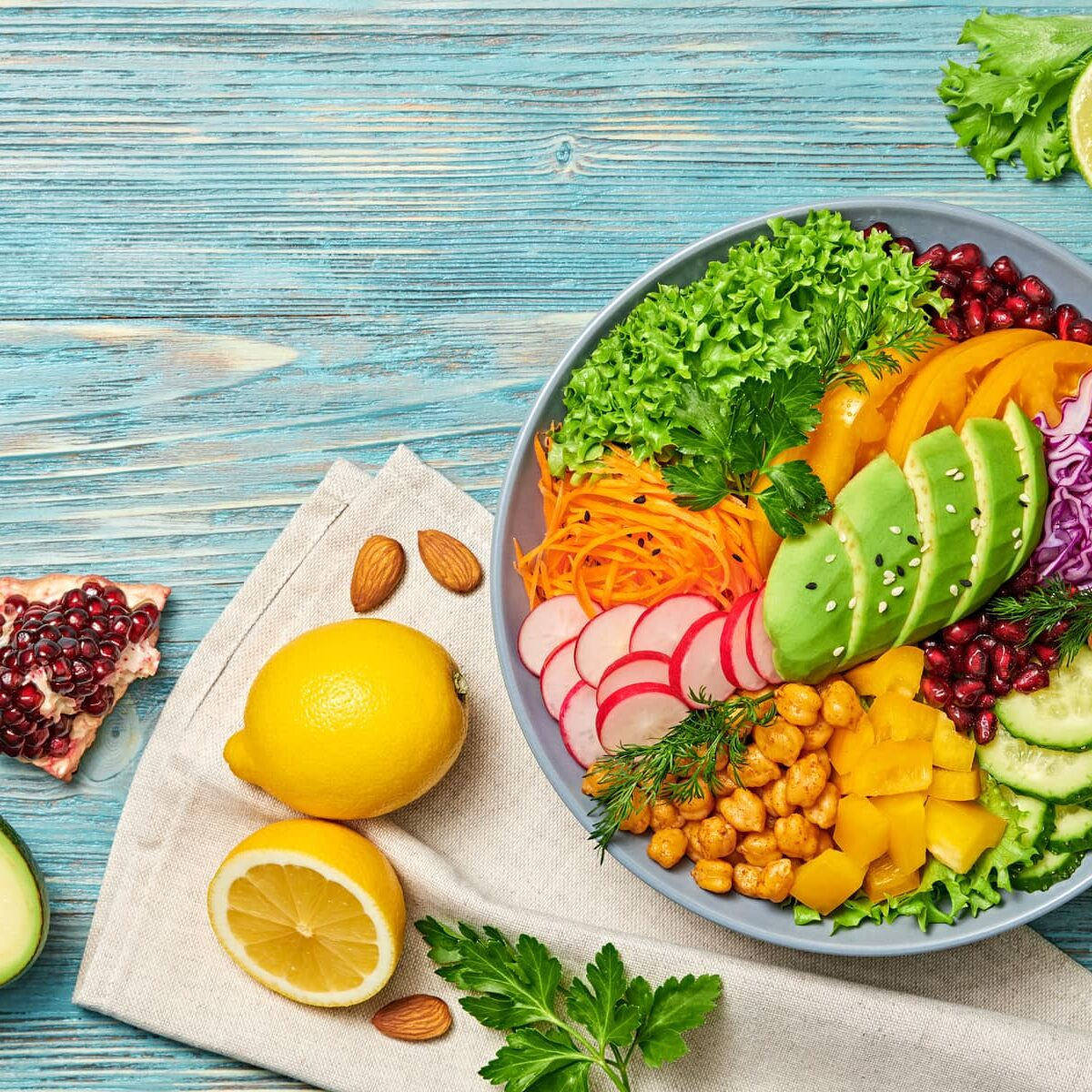 Buddha bowl salad with avocado, tomato, lettuce, cucumber, red cabbage, chickpeas, pomegranate. Paleo diet, healthy vegan and balanced food concept. Fresh rainbow mix green salad on blue wood